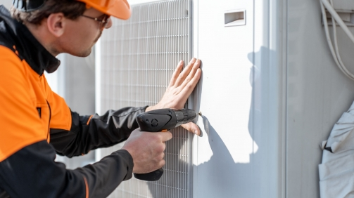 Professional workman in protective clothing installing or reparing outdoor unit of the air conditioner or heat pump on the rooftop